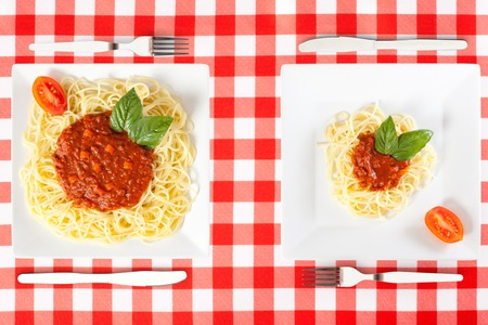 two plates of spaghetti, one large portion and one small portion
