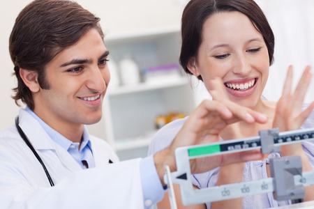 male doctor weighing happy female patient